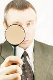 O homem olha através de uma lupa Fotografia de Stock Royalty Free