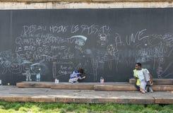 O homem olha a criança tirar no quadro-negro exterior, Paris Fotos de Stock