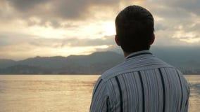 O homem olha em uma camisa que olha o nascer do sol na praia do oceano O sol aumenta atrás das montanhas E filme