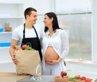O homem olha lovingly no seu grávido foto de stock