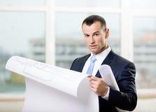 O homem olha o modelo nas mãos Fotografia de Stock