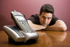 O homem olha o telefone. Espera Imagens de Stock