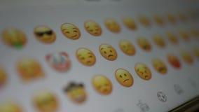O homem olha os ícones do emoji em um smartphone vídeos de arquivo