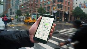 O homem olha o passeio que compartilha de testes padrões de tráfego em Smartphone vídeos de arquivo