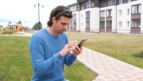 O homem olha redes sociais na tela de um telefone celular vídeos de arquivo