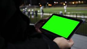 O homem olha a tabuleta verde da tela em um futebol Team Practice Session da bancada - ângulo ascendente próximo filme