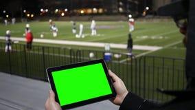 O homem olha a tabuleta verde da tela em um futebol Team Practice Session da bancada V2 vídeos de arquivo