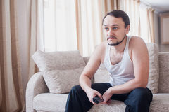 O homem olha transferência interessante na tevê Fotografia de Stock Royalty Free