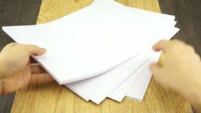 O homem organiza o papel vazio no fundo de madeira vídeos de arquivo