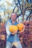 O homem orgulhoso está com as duas abóboras enormes em suas mãos Fotografia de Stock