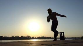 O homem otimista dança o disco em um banco de rio no verão no slo-mo vídeos de arquivo