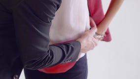 O homem põe o bloco de nádegas vermelho sobre os quadris do modelo vídeos de arquivo