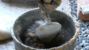 O homem põe o cimento em uma cubeta do ferro com areia para obter um almofariz video estoque