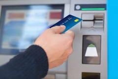 O homem põe o cartão de crédito no ATM Foto de Stock