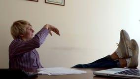 O homem põe seus pés sobre uma tabela, desintegra seu Doc, lances ele afastado em um escritório vídeos de arquivo