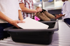 O homem põe a tabuleta de Digitas em Tray For Airport Security Check Imagem de Stock Royalty Free