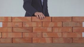 O homem põe o tijolo na parede vídeos de arquivo