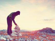 O homem pôs o último intopeak de pedra da pirâmide Pirâmide de pedra equilibrada na cimeira da montanha Imagem de Stock