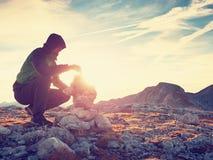 O homem pôs o último intopeak de pedra da pirâmide Pirâmide de pedra equilibrada na cimeira da montanha Fotografia de Stock