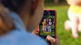 O homem pai tira fotos de sua família, esposa alegre, filho e filha video estoque