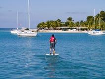 O homem peddle sobre o barco nos tropics Imagens de Stock Royalty Free