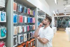 O homem pensativo escolhe caixas para um smartphone no departamento dos acessórios na loja moderna da eletrônica foto de stock