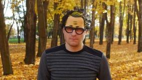 O homem pensativo ou descontentado em uma máscara está no parque do outono Queda da folha em uma cidade no dia ensolarado Naturez filme