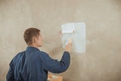 O homem pinta a parede Imagem de Stock