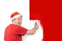 O homem pinta uma escova do rolo da parede com um vermelho Imagem de Stock