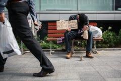 O homem pobre e bêbado está sentando-se no banco e guardando um cartão que diga os sem abrigo ajudam por favor Pôs a cabeça dispo foto de stock