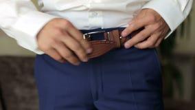 O homem prende a correia em sua calças, close-up video estoque