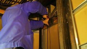 O homem prende equipamentos eletrônicos à parede filme