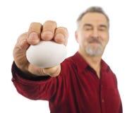 O homem prende o ovo branco em sua mão outstretched. Fotografia de Stock