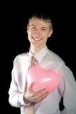 O homem prende um balão cor-de-rosa do coração Fotografia de Stock Royalty Free