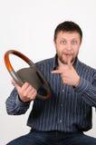 O homem prende uma roda em uma mão e mostra nela a Imagem de Stock Royalty Free