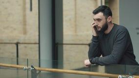 O homem preocupado fala em seu Smartphone no salão video estoque