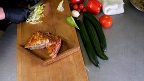 O homem prepara o almoço, serve o petisco grelhado do sanduíche do pão sobre a placa de corte de madeira, com lado da salada verd filme
