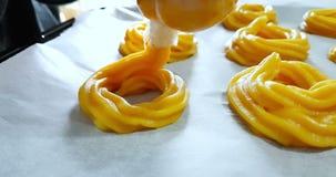 O homem prepara as sobremesas de creme deliciosas chamadas zeppole de St Joseph em uma bandeja de cozimento com um saccapoche, tr
