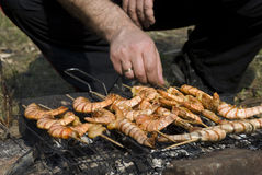 O homem prepara camarões em uma grade Imagens de Stock