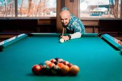O homem prepara-se para despedaçar a pirâmide de bolas de bilhar na tabela Foto de Stock Royalty Free