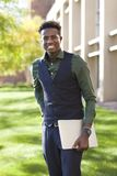 O homem preto novo considerável do estudante sorri estando no acampamento da faculdade Imagens de Stock Royalty Free