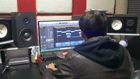 O homem produz a música eletrônica no projeto em um estúdio de produção vídeos de arquivo
