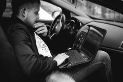 O homem profissional com um portátil no carro ajusta o sistema de controlo de ajustamento, actualizando o software, acedendo comp Foto de Stock Royalty Free