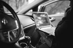 O homem profissional com um portátil no carro ajusta o sistema de controlo de ajustamento, actualizando o software, acedendo comp Fotografia de Stock Royalty Free