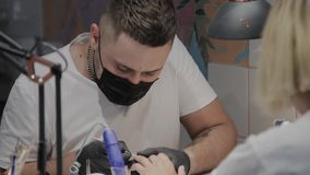 O homem profissional do manicuro aumenta cutículas para a ferramenta especial de um udvivaniya mais adicional vídeos de arquivo