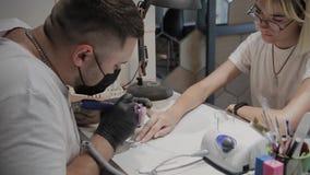 O homem profissional do manicuro aumenta cutículas para a ferramenta especial de um udvivaniya mais adicional filme