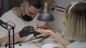 O homem profissional do manicuro aumenta cutículas para a ferramenta especial de um udvivaniya mais adicional video estoque