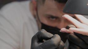 O homem profissional do manicuro enverniza os pregos de uma menina video estoque