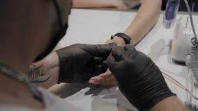 O homem profissional do manicuro fricciona seus pés com um pano anestésico video estoque