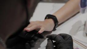 O homem profissional do manicuro fricciona seus pés com um pano anestésico vídeos de arquivo